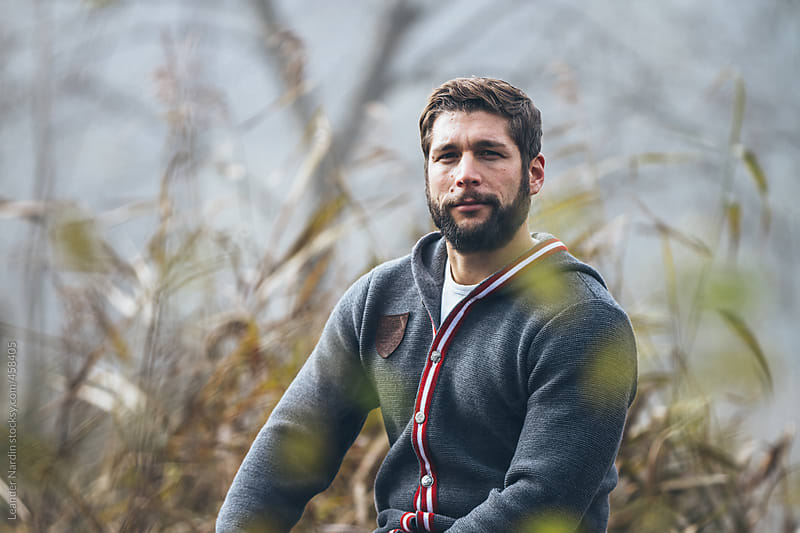 portrait of a bearded young man outdoors  by Leander Nardin for Stocksy United