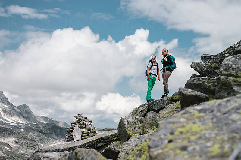 two female hiker standing and overlooking the high alpine scenery by Leander Nardin for Stocksy United