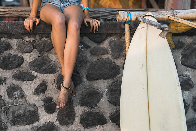 Young Woman Sitting Next Her Surfboard by Alexander Grabchilev for Stocksy United