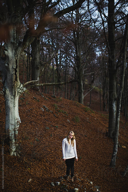 Girl walking in an autumn forest by michela ravasio for Stocksy United