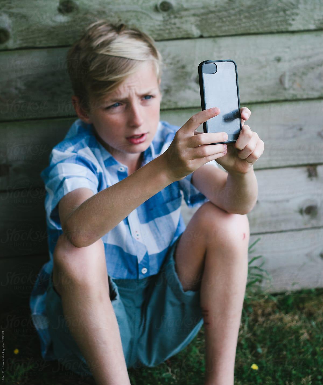 A Tween Boy Taking A Selfie With A Smartphone By Helen -9080