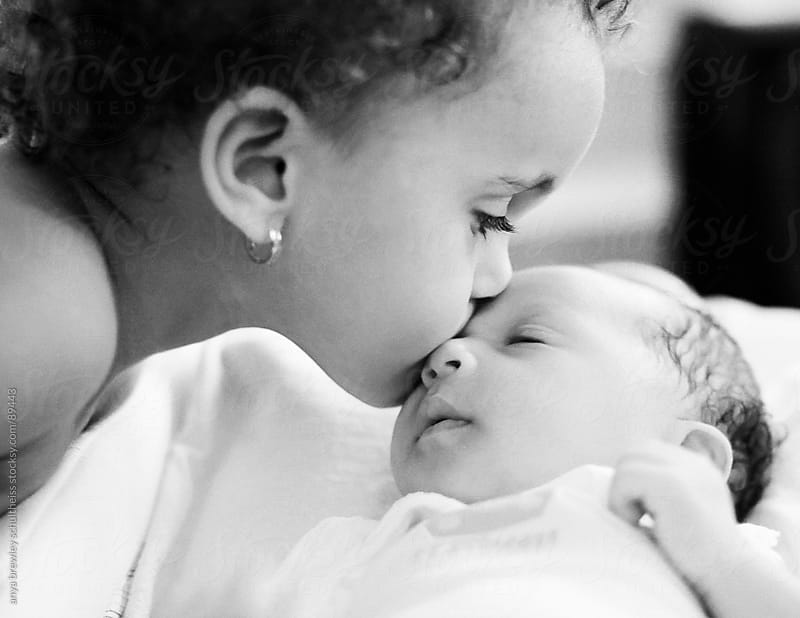 Portrait of a toddler tenderly kissing her newborn sister. by anya brewley schultheiss for Stocksy United
