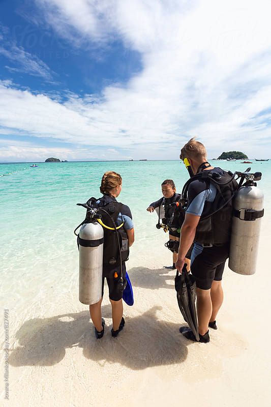 Beautiful young couple having Scuba Diving course with their instructor in tropics by Jovana Milanko for Stocksy United
