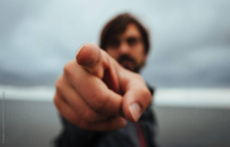 Man Pointing in the Direction of the Camera, Shallow Depth of Field by Claudia Lommel for Stocksy United