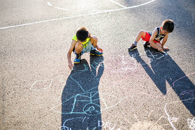 Asian kids drawing with chalk on the ground in the playground by Suprijono Suharjoto for Stocksy United