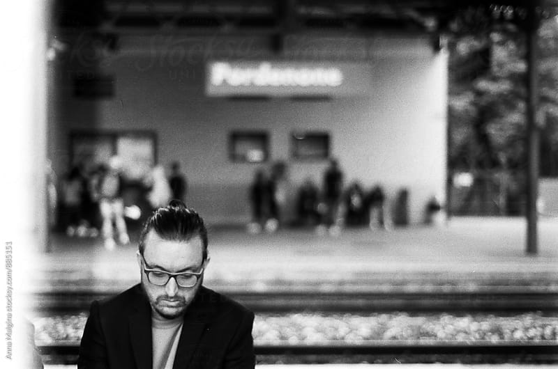 A black and white film photo of man waiting the train by Anna Malgina for Stocksy United