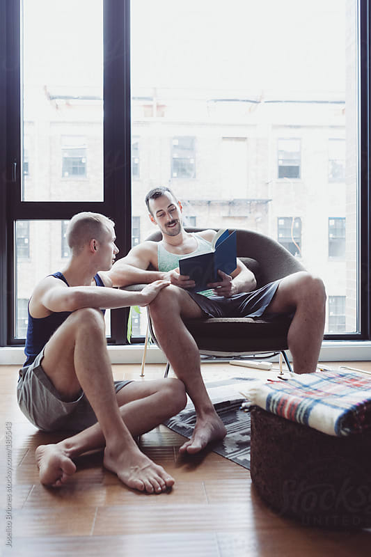 Gay Male White Couple Relaxing at Home Reading on a Weekend by Joselito Briones for Stocksy United