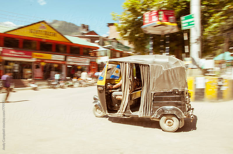 A motorised tuk-tuk travelling through an Indian village by Andy Campbell for Stocksy United
