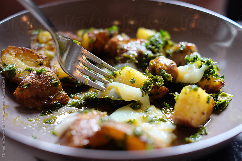 A delectable dish of herb infused potato hash by Maximilian Guy McNair MacEwan for Stocksy United