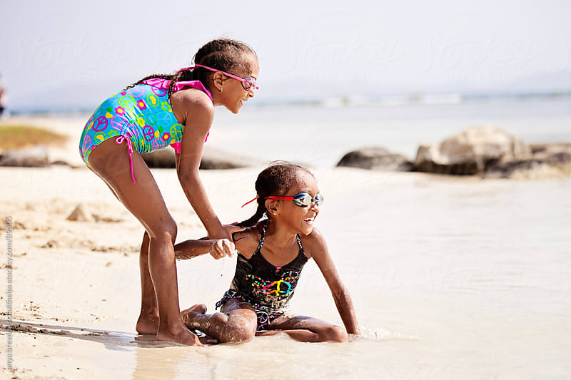 Portrait of two sisters playing happily on a sandy white beach by anya brewley schultheiss for Stocksy United