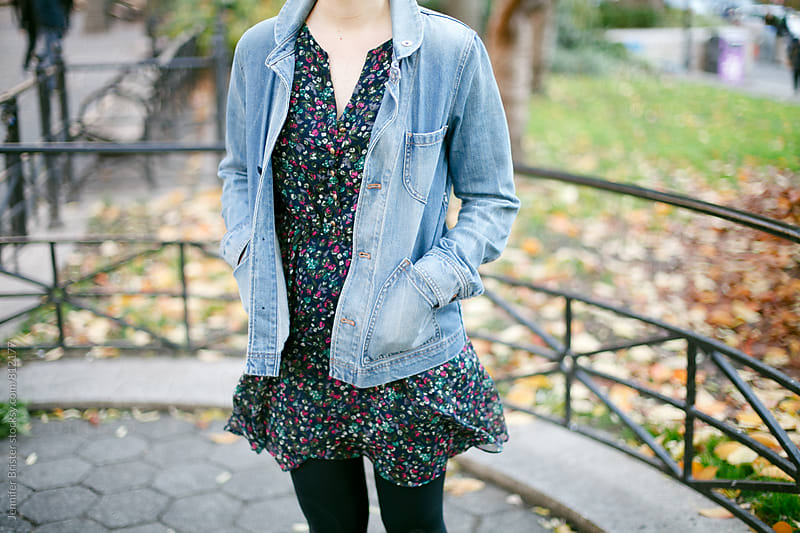 Woman holds hands in pocket of jean jacket by Jen Brister for Stocksy United