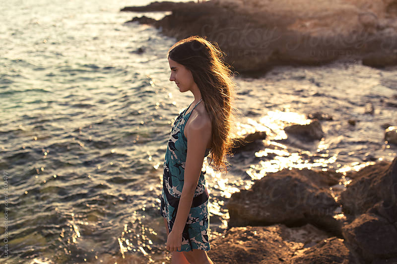 Beautiful young woman looking at the sea by Lucas Ottone for Stocksy United