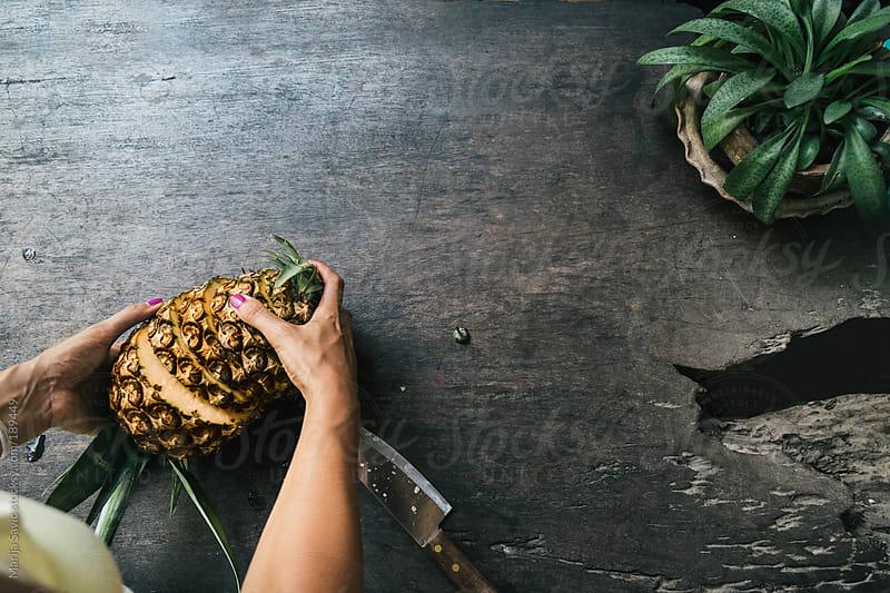 Woman Cutting Pineapple  by Marija Savic for Stocksy United