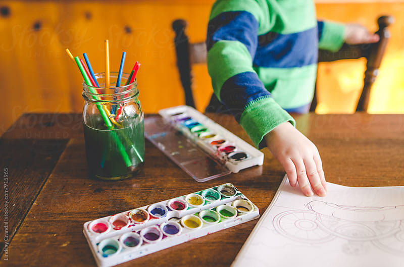 Young child painting with watercolors by Lindsay Crandall for Stocksy United