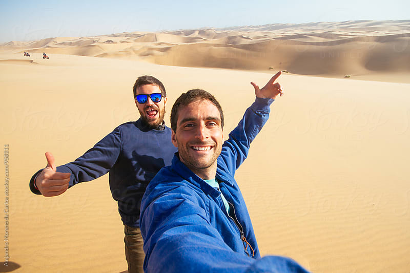 Two handsome men in sand dunes by Alejandro Moreno de Carlos for Stocksy United
