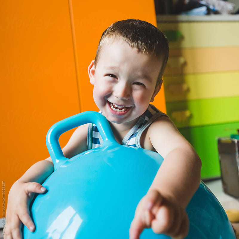Happy Male Toddler at Home Playing with a Big Jumping Ball by Giorgio Magini for Stocksy United
