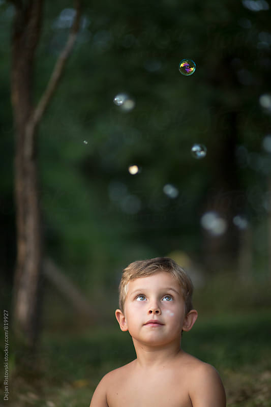 Boy looking bubble wand. by Dejan Ristovski for Stocksy United