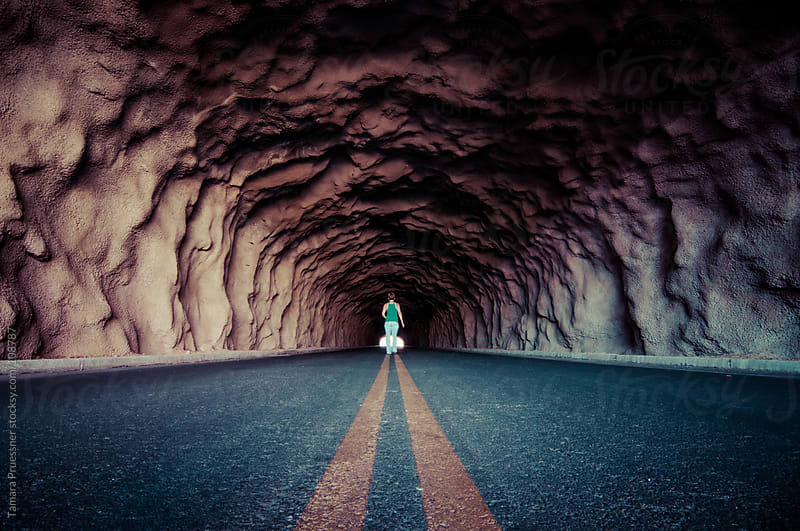 Woman In The Distance In A Tunnel by Tamara Pruessner for Stocksy United