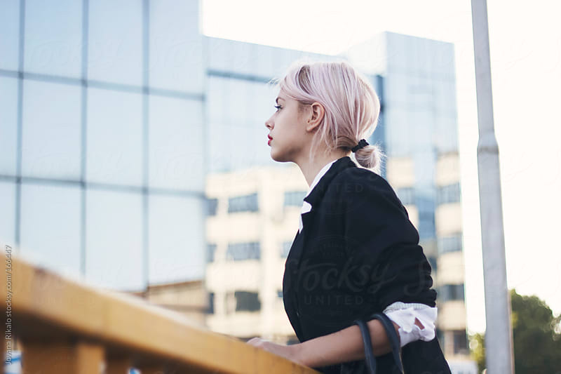 Young businesswoman standing in front of glass building by Jovana Rikalo for Stocksy United