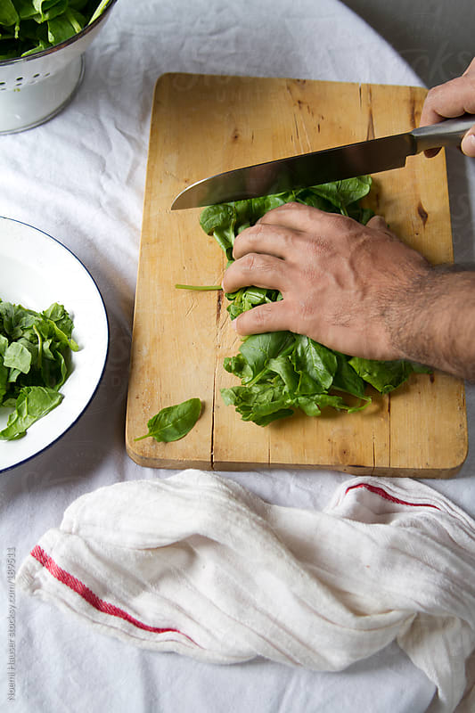 Man chopping spinach by Noemi Hauser for Stocksy United