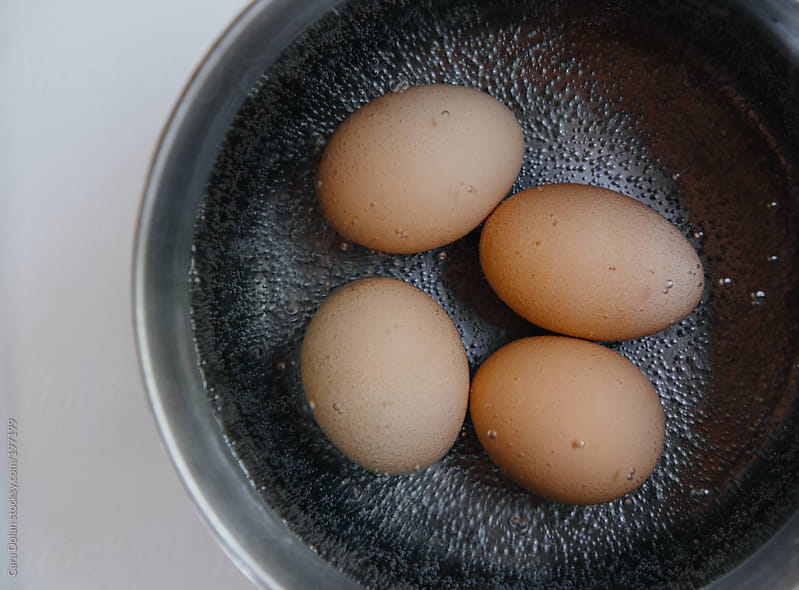 Four eggs boil in a pot of water on the stove by Cara Dolan for Stocksy United