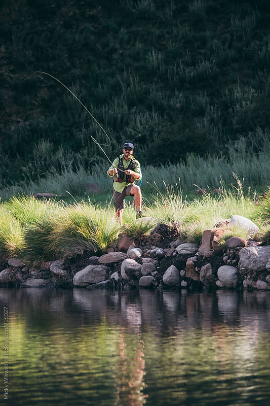Fly fisherman casting in a river by Micky Wiswedel for Stocksy United