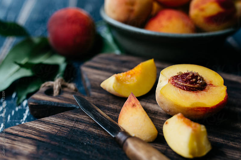 Fresh peaches cut on a board by Gabriel (Gabi) Bucataru for Stocksy United