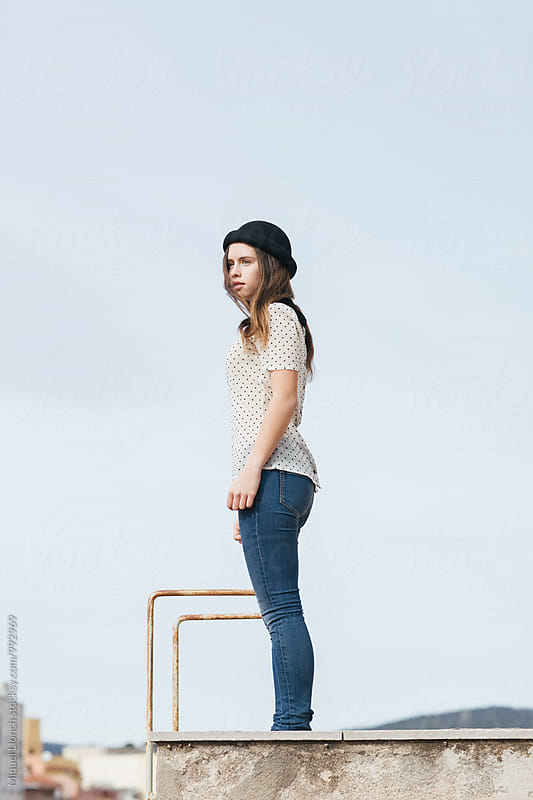 Beautiful young woman standing on rooftop by Miquel Llonch for Stocksy United
