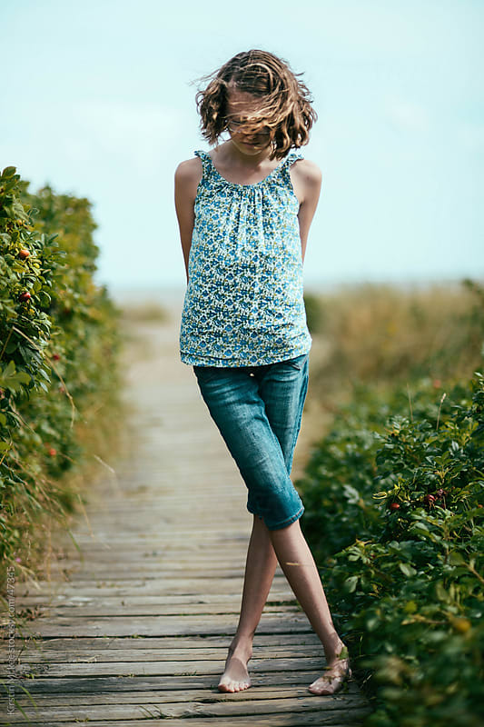 Caucasian girl on a boardwalk by Kirstin Mckee for Stocksy United