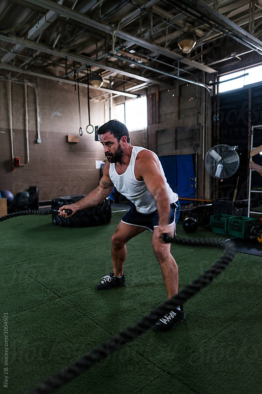 Muscular man using battling ropes in gritty gym by Riley Joseph for Stocksy United
