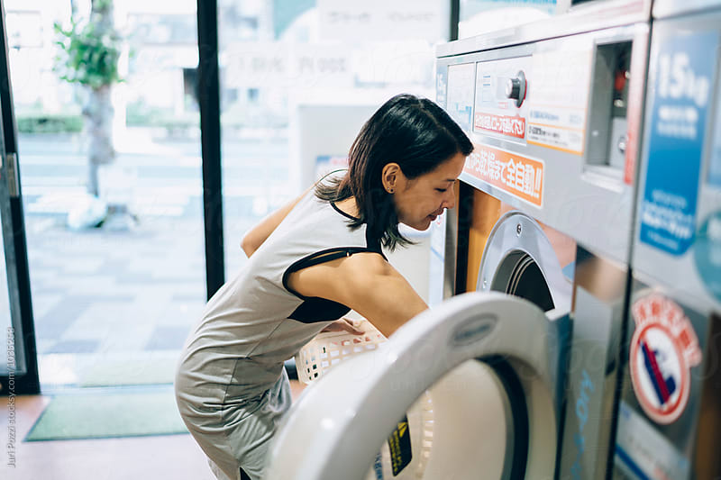Young Asian Woman loading a washing machine in Kobe Japan by Juri Pozzi for Stocksy United