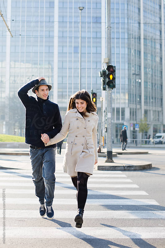 Young couple runs to cross the road by michela ravasio for Stocksy United