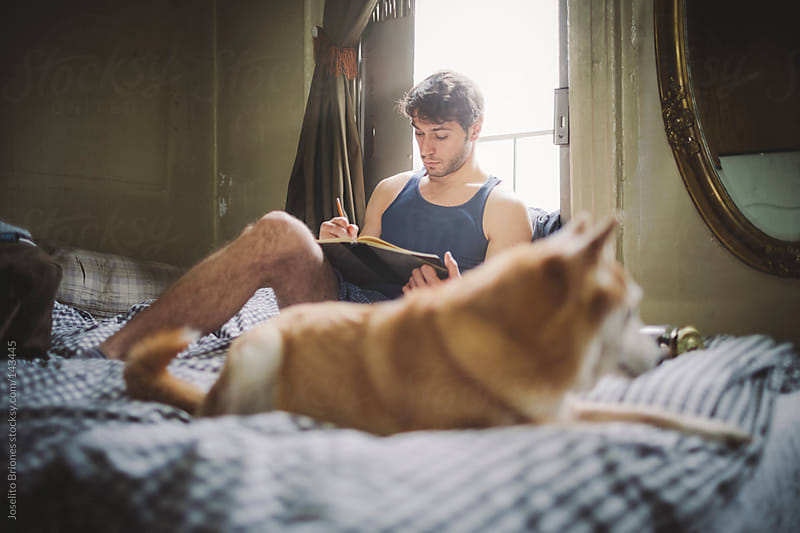 Man Writes in Notebook in Bed at Home with Pet Dog by Joselito Briones for Stocksy United