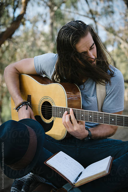 Musician playing a few chords for his new song he just wrote in his notebook by Emmanuel Hidalgo for Stocksy United