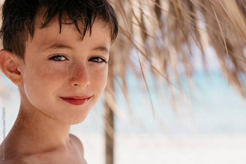 Headshot of a smiling boy looking at camera in a tropical Summer environment by Beatrix Boros for Stocksy United