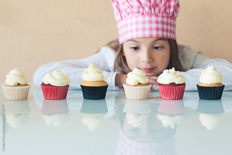 Little girl in cook hat staring at row of cupcakes by Cindy Prins for Stocksy United