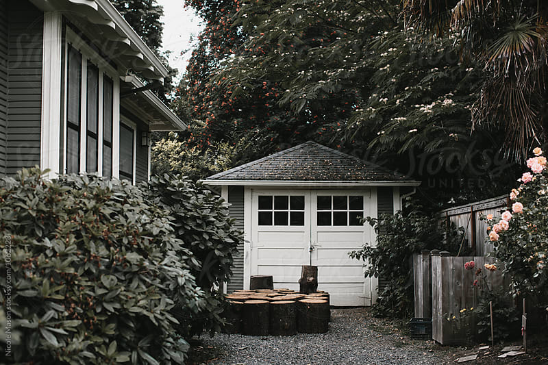 garage next to house surrounded by greenery by Nicole Mason for Stocksy United