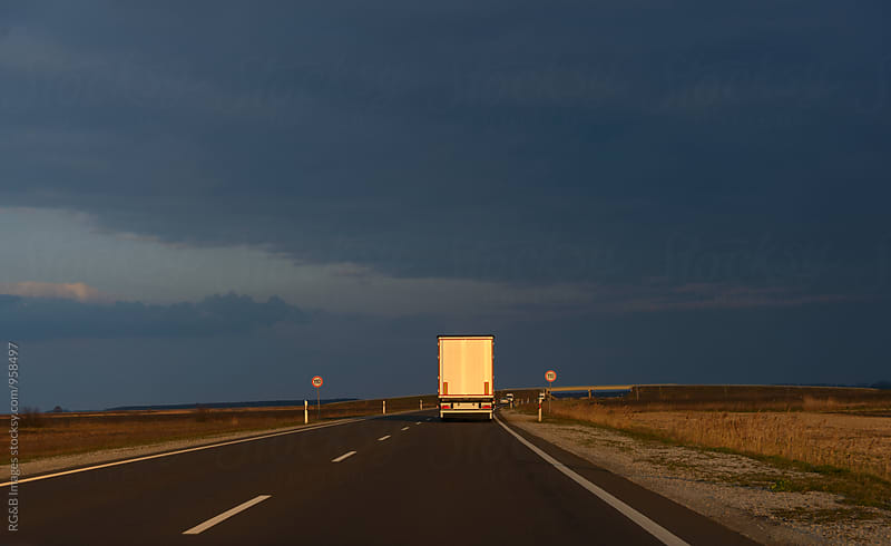 Cargo truck driving on the road in sunlight by RG&B Images for Stocksy United