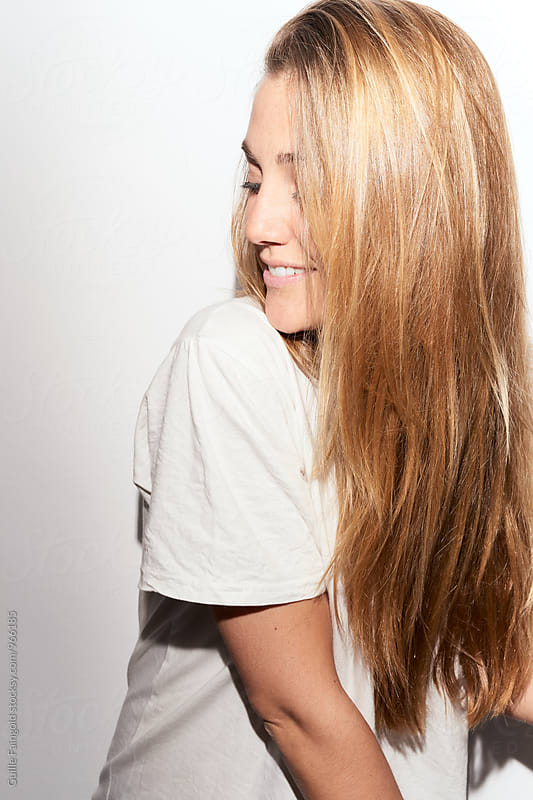 Close-up of smiling blonde girl looking down by Guille Faingold for Stocksy United