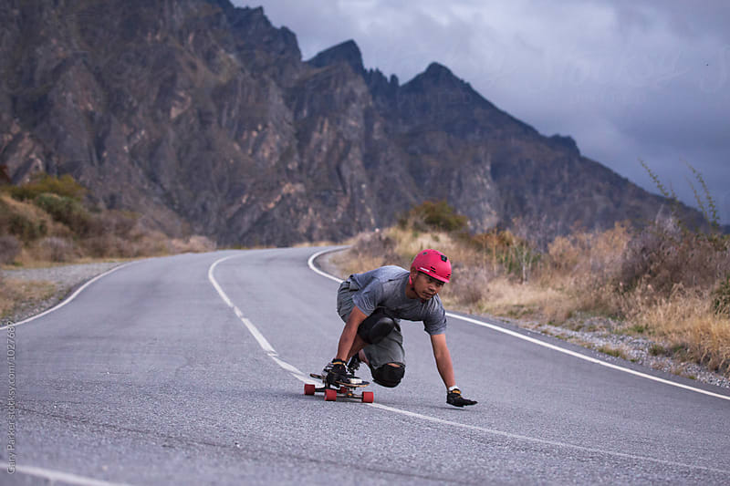 Skateboarder bombing a big hill in New Zealand by Gary Parker for Stocksy United