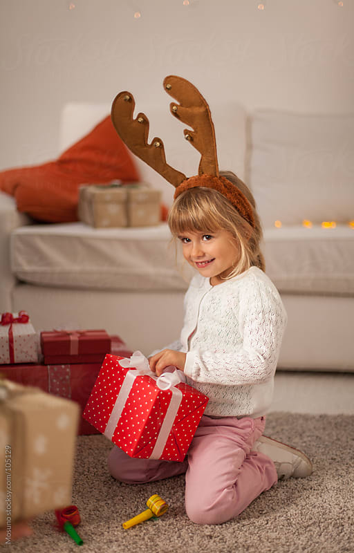 Little Girl Opening Christmas Present by Mosuno for Stocksy United