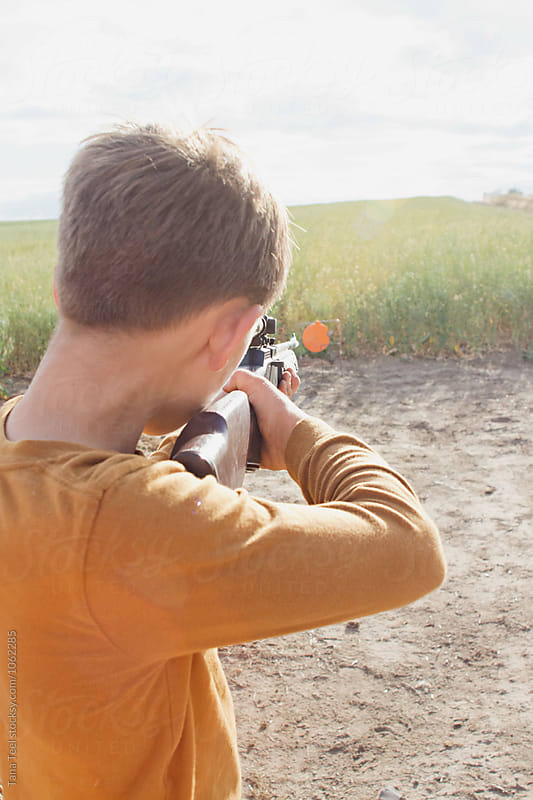 boy aiming bb gun at target in field by Tana Teel for Stocksy United