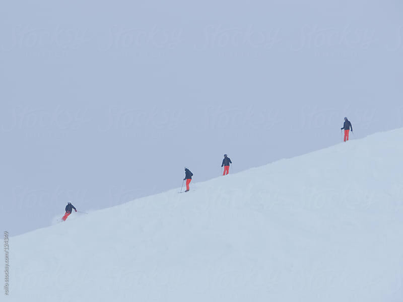 Skiers descending a ski slope on a cold winter day by rolfo for Stocksy United