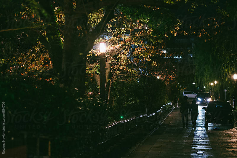 Laneway with anonymous couple walking at night in Gion District, Kyoto by Rowena Naylor for Stocksy United