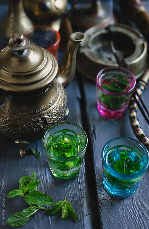 Freshly made mint tea in small colorful glasses,surrounded by condiments.  by Darren Muir for Stocksy United