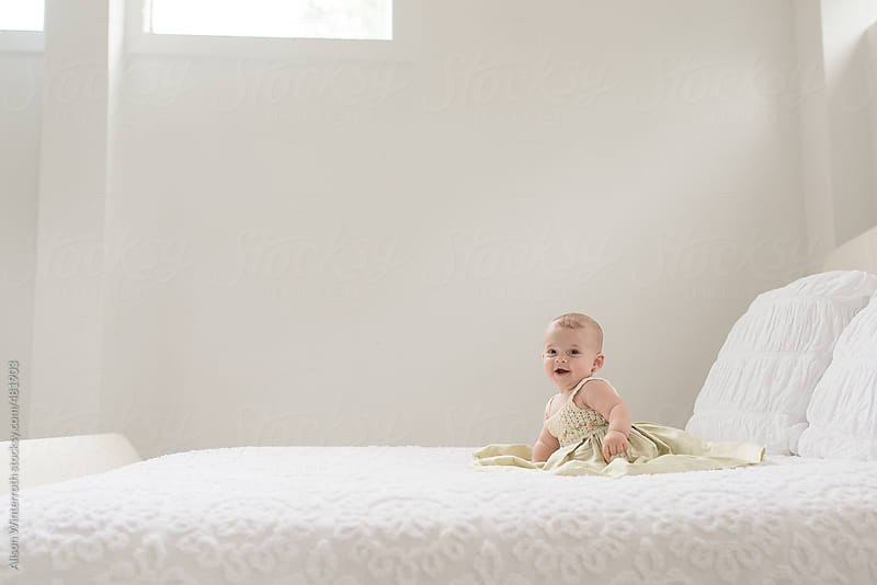 Baby Girl In Nice Dress Alone On A Bed by Alison Winterroth for Stocksy United