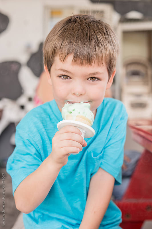 Young Boy Eats an Ice Cream Cone on a Hot Summer Day by suzanne clements for Stocksy United