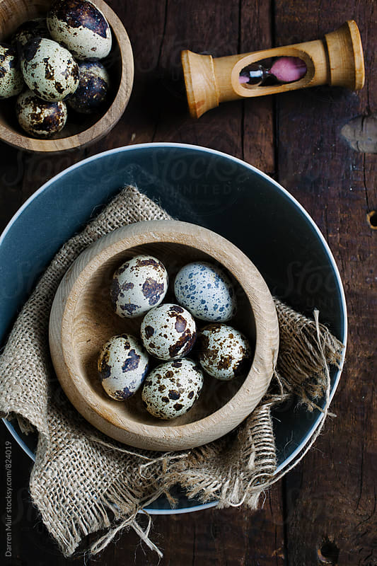 Quail eggs in bowls on a wooden background with an egg timer.  by Darren Muir for Stocksy United
