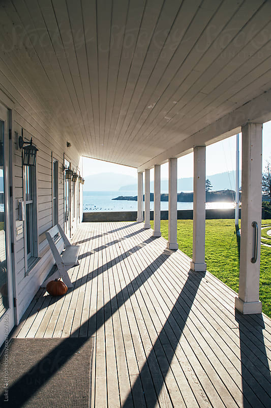 Front Porch Drenched In Sunlight And Shadow Near Seashore by Luke Mattson for Stocksy United