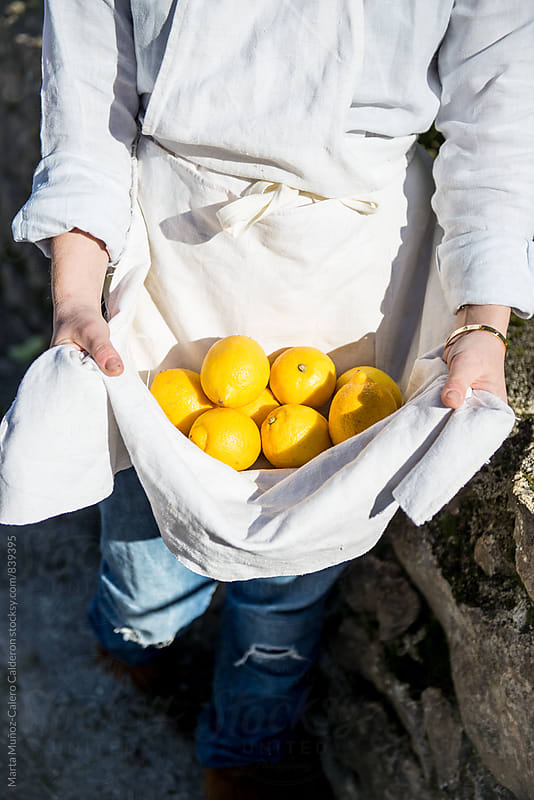 Girl carring Lemons in her linen apron by Marta Muñoz-Calero Calderon for Stocksy United